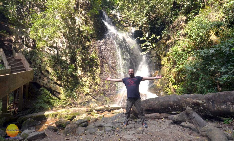 white man with arms outstretched under the Erin-ijesha waterfalls in Nigeria