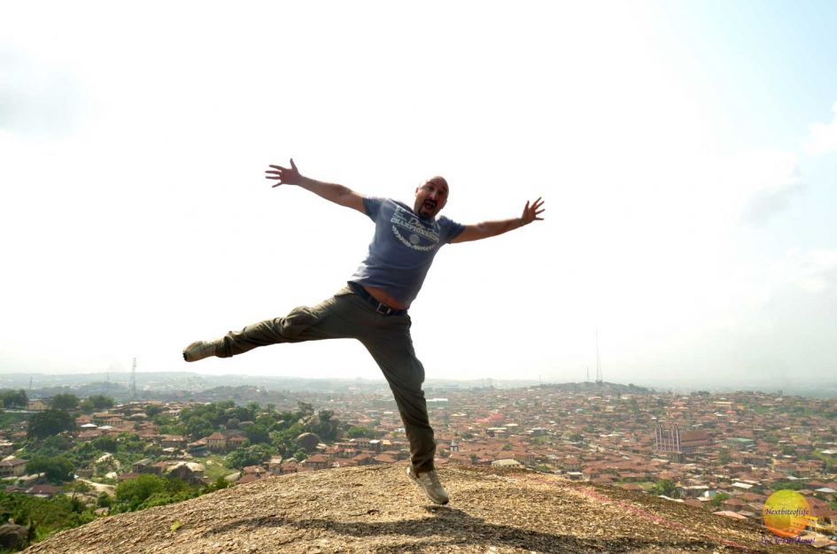 white man jumping for joy at the top of Olumo Rock Nigeria