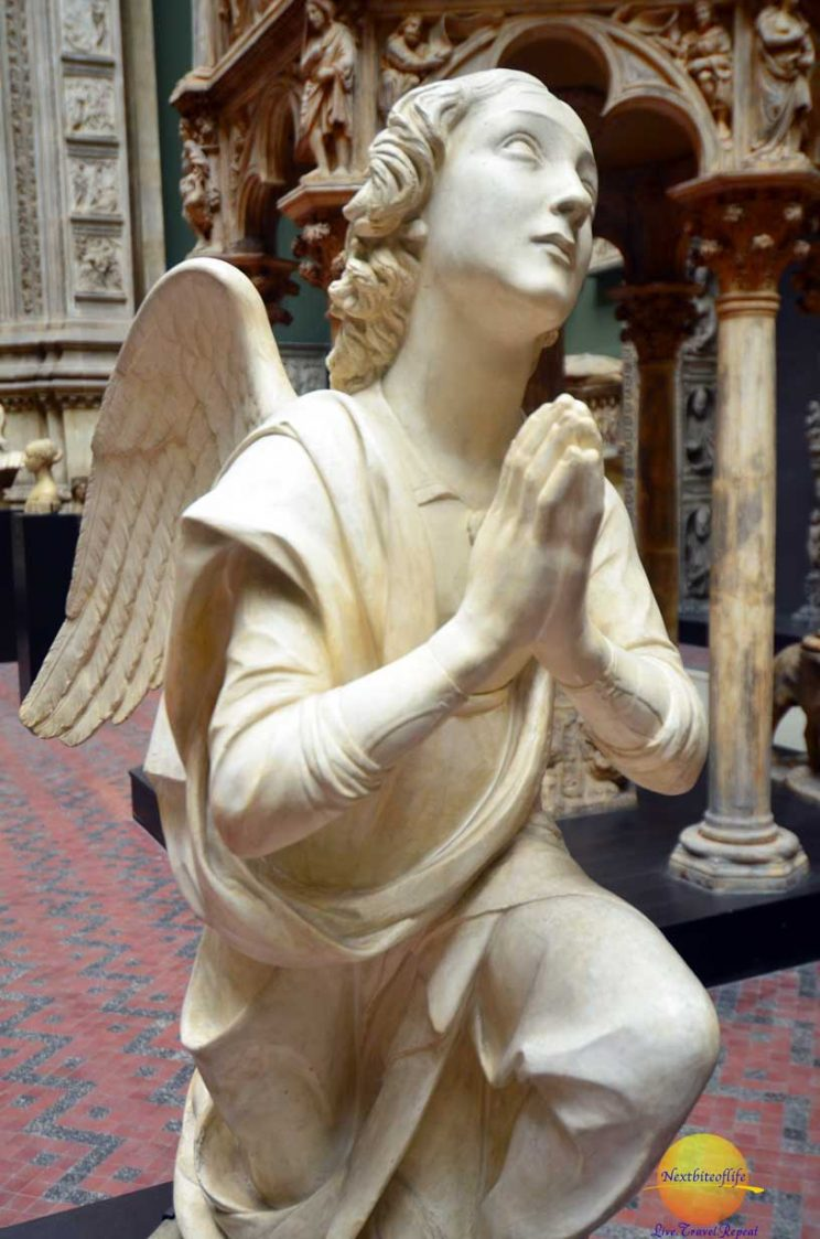 Angel with hands in prayer sculpture at Albert and Victoria museum
