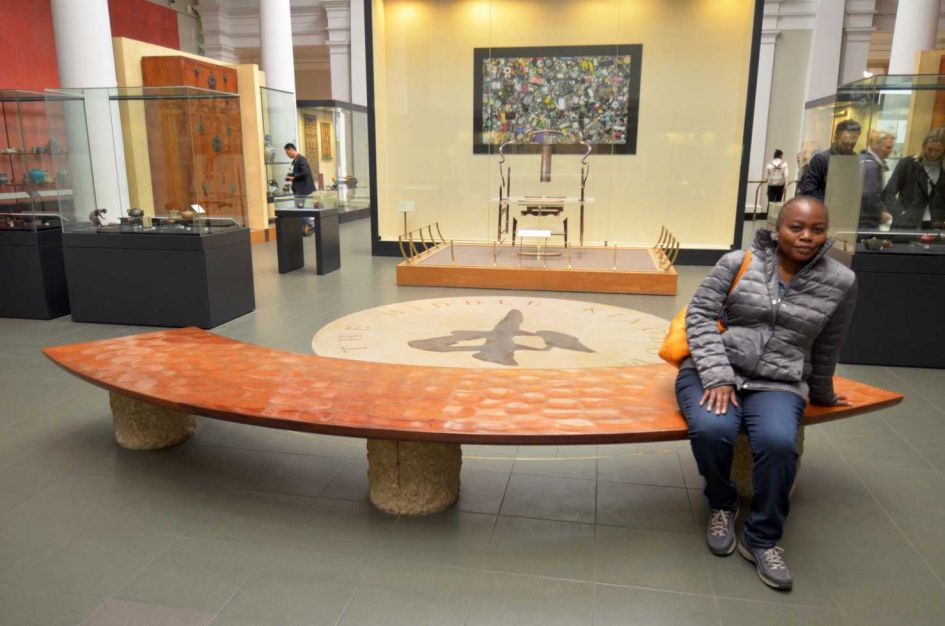 woman sitting on curved bench inside Victoria and Albert museum London