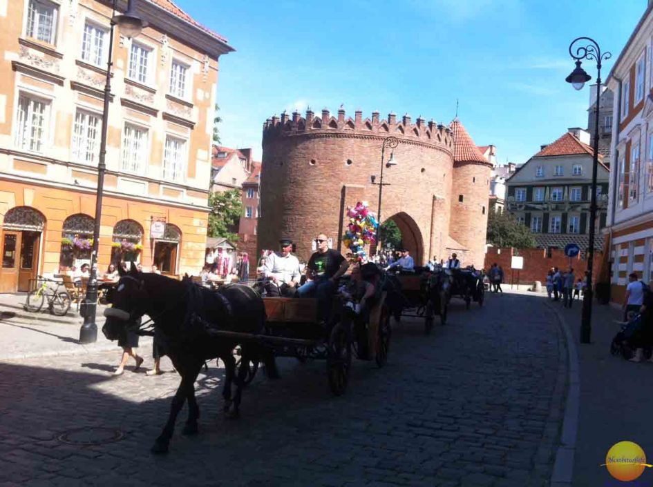people on carriage rides by Barbican castle in Warsaw