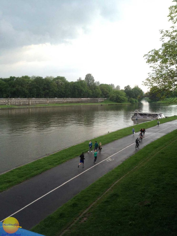 Krakow park with joggers on cloudy day with river view