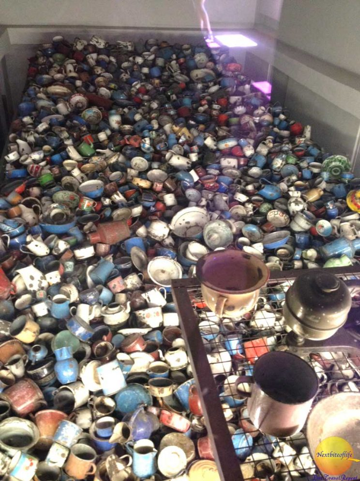 soup bowls collection behind glass at Auschwitz concentration camp