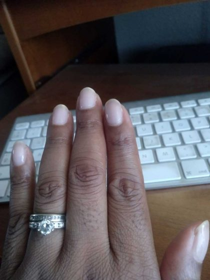 Black woman's left hand with diamond ring on keyboard