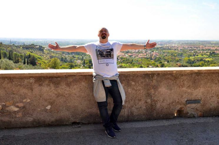 man with arms outstretched at villa deste Tivoli