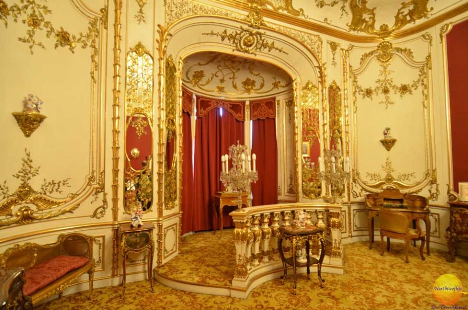 Gold gilded room with red curtains inside Peles Castle Romania