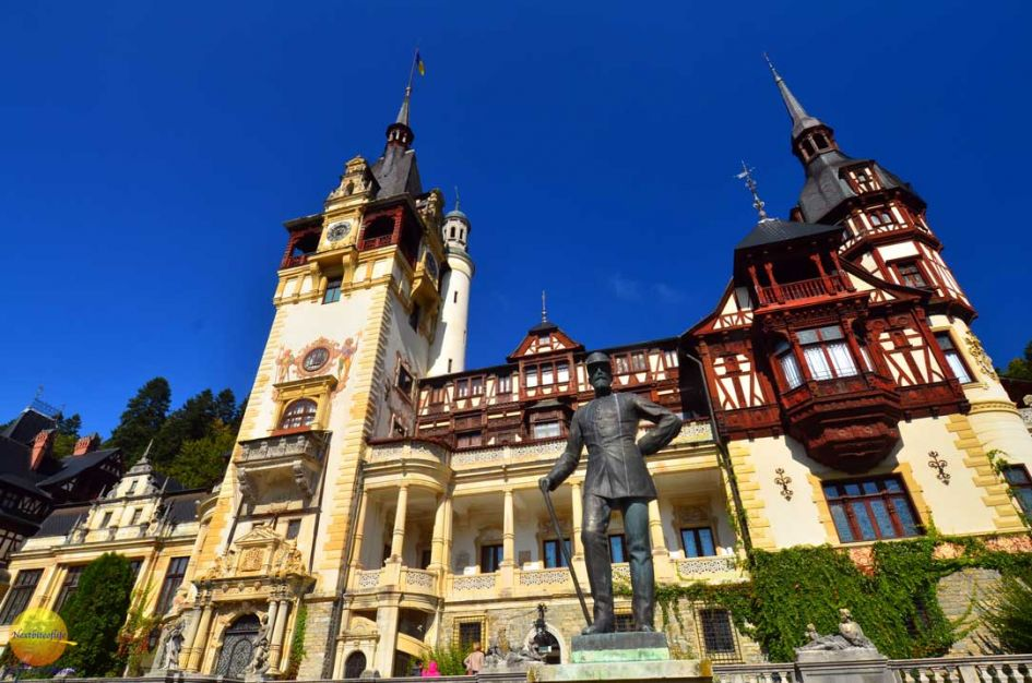 Peles castle Romania front with statue and blue skies