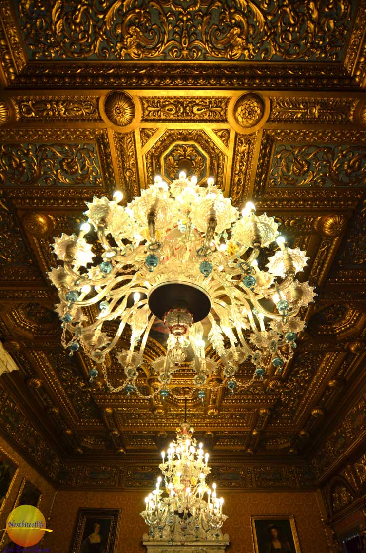 interior gold chandelier and gold coffed ceiling