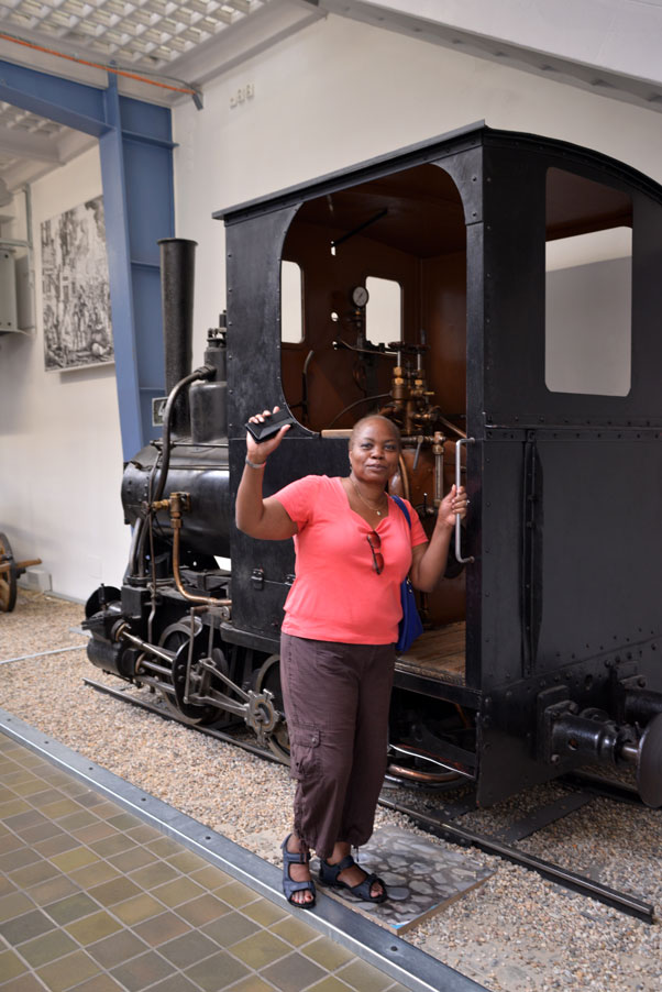 woman waving from steam train on track front at national Technical Museum Prague