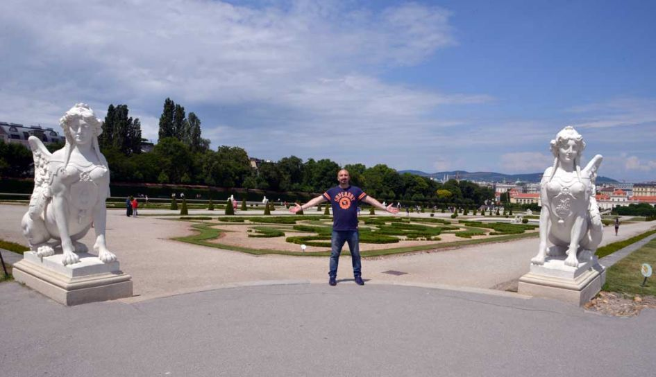 man in belvedere gardens Vienna with arms outstretched