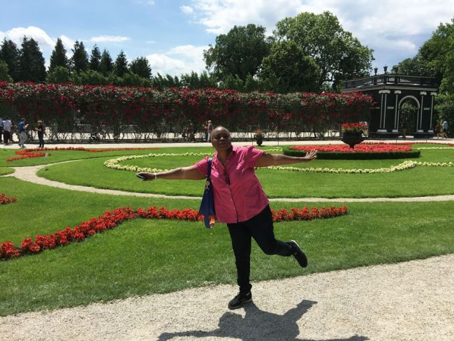 Schonbrunn gardens woman in ink shirt with arms outstretched