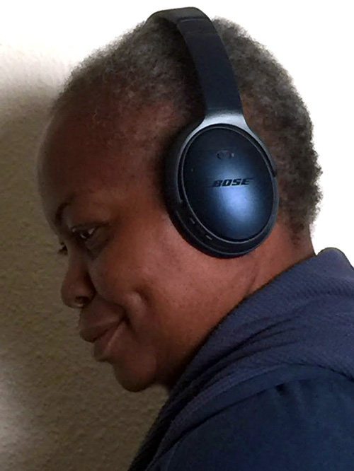 side view black woman with blue Bose CC35 wireless headphones