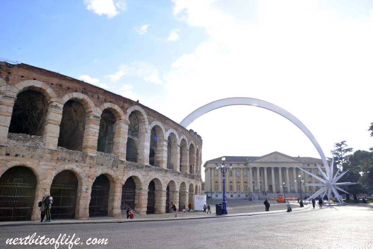 Arena di Verona and government building with arch.