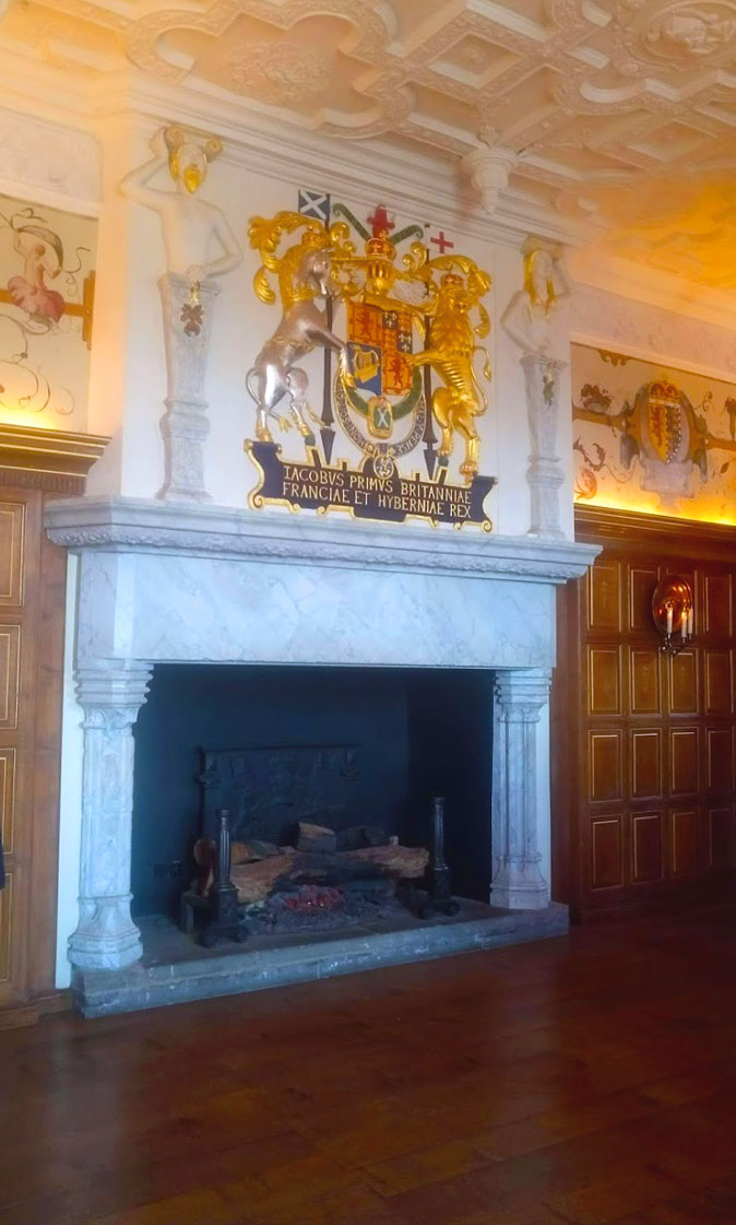 Laich hall interior in Edinburgh castle with fireplace and royal crest above it.