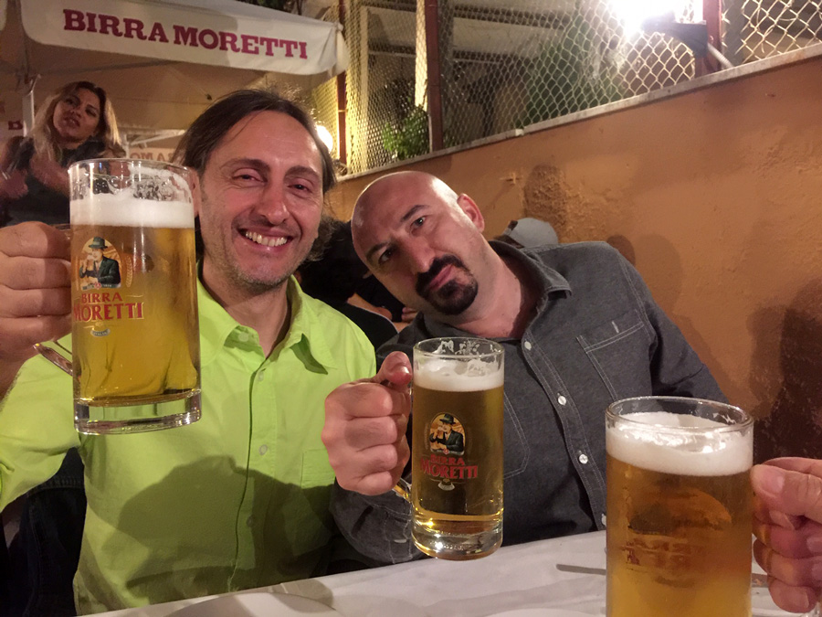 2 male friends posing with mugs of beer. Rome in the fall enjoyment