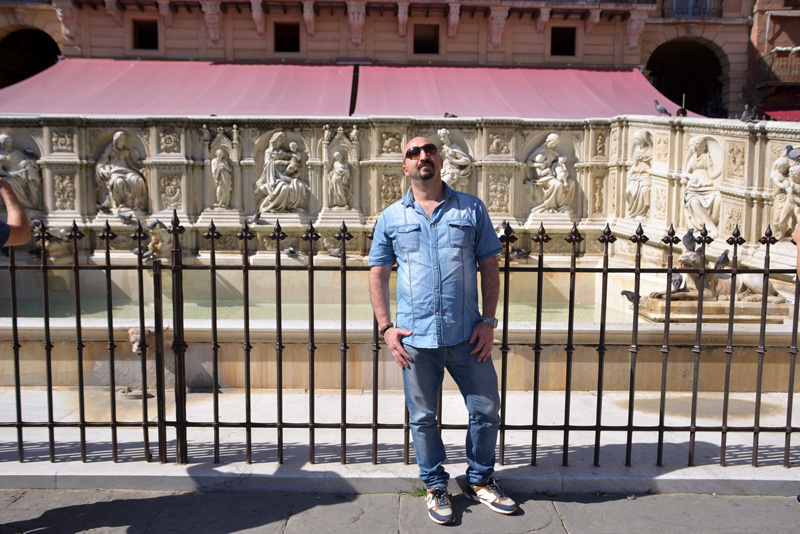 Man posing in jeans shirt and pants in front of fountain in Siena piazza del campo