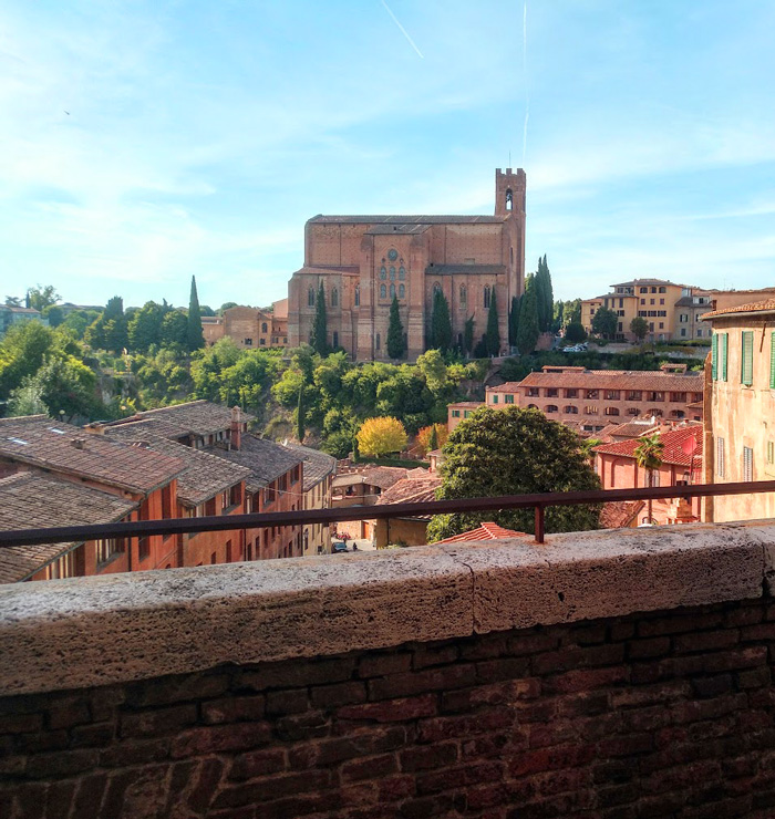 view from the bridge towards basilica san domenico in the rear, one of 12 reasons to visit siena in the fall