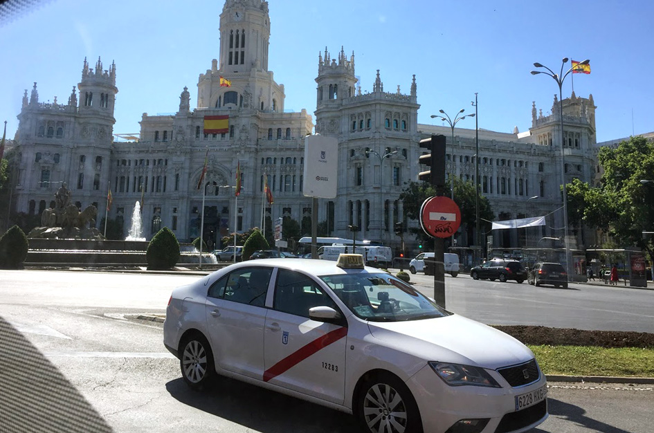 white cab in Madrid and plaza Cibeles in the rear. Tipping in Spain guide
