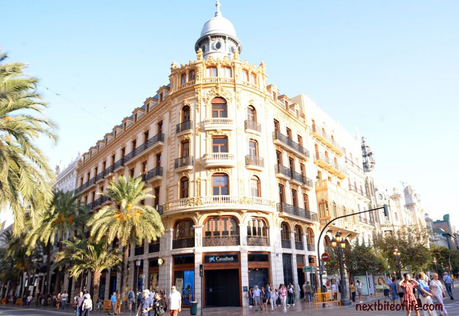 building in downtown Valencia with people walking and Caixa bank in rear