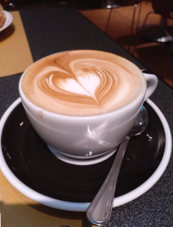 cup of cappuccino and foam with heart black saucer in our tipping in Spain guide