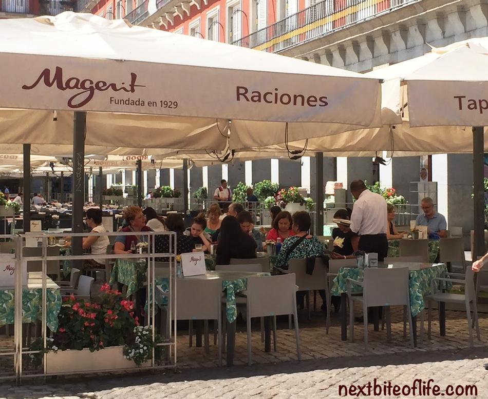 People dining at Plaza Mayor Spain under white umbrellas