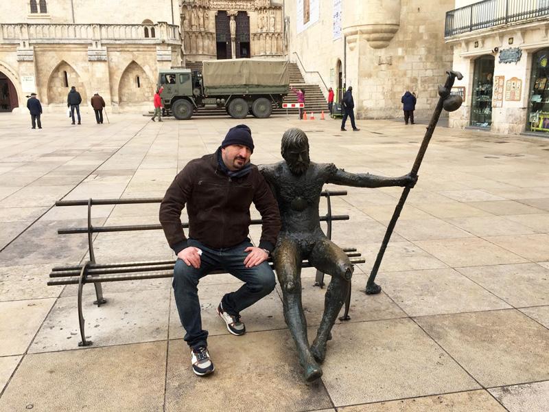 man sitting next to pilgrim statue at Burgos cathedral Spain