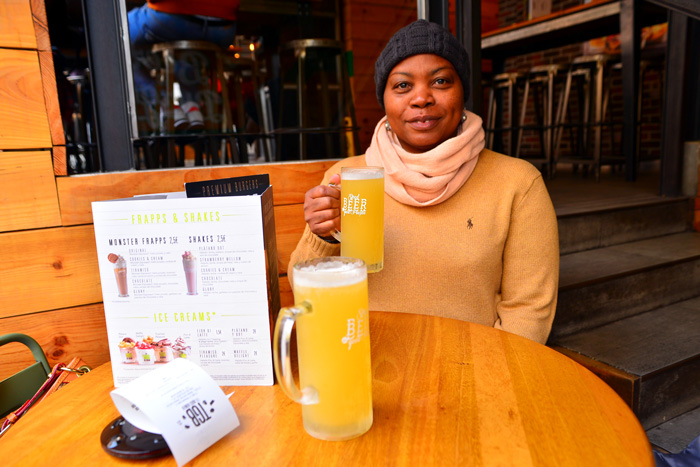 the good burger salamanca with black female in cream sweater holding a mug of beer