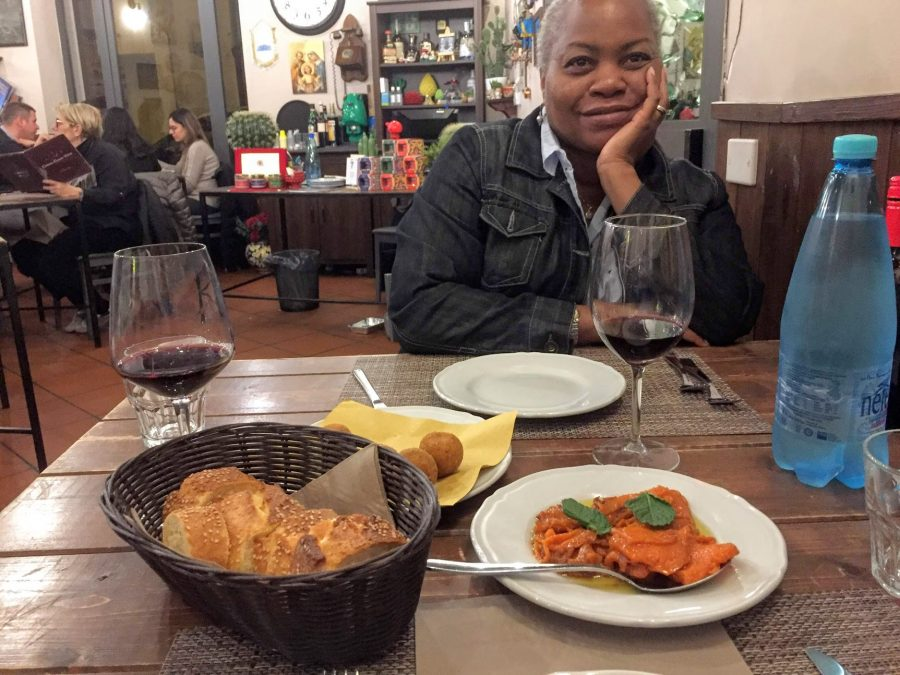 woman sitting at table in cafe with pumpkin appetizer and arancini on travel in the age of coronavirus