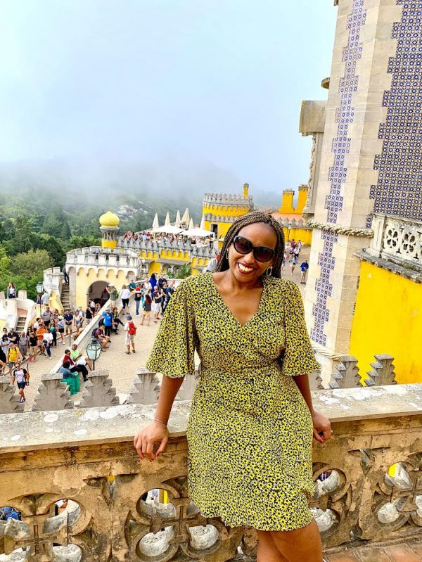 black woman in braids green dress with Sintra castle in the background