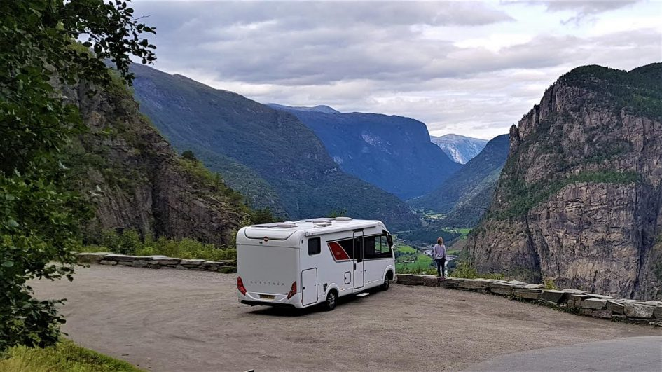 rv van parked with mountain views and woman posing