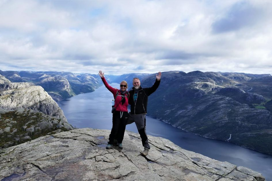 couple in northern Europe with mountain and water view behind themh