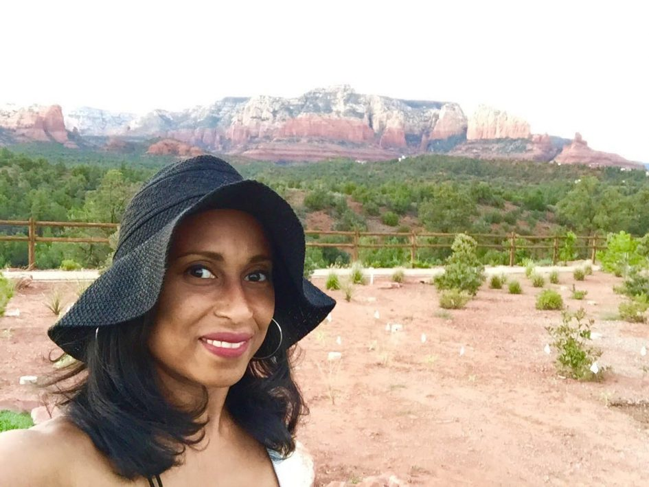 woman with red rocks in the background wearing black sun hat