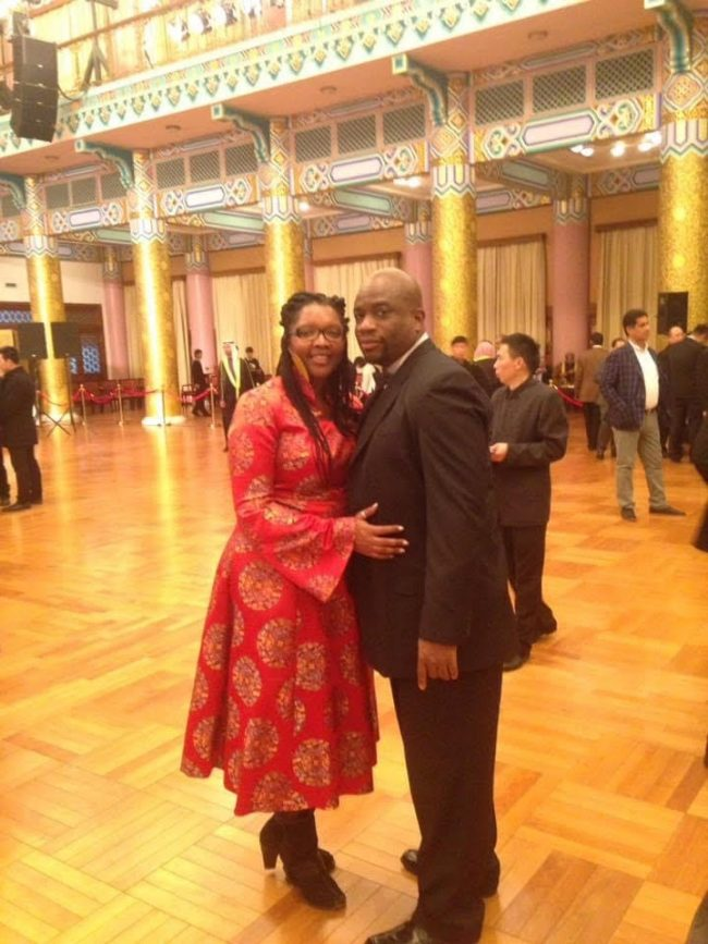 hubby and wife at function him in black suit, her in red dress