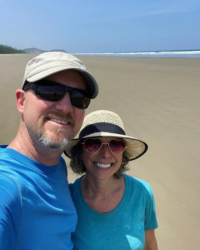 Man and woman in hats on beach in Ecuador